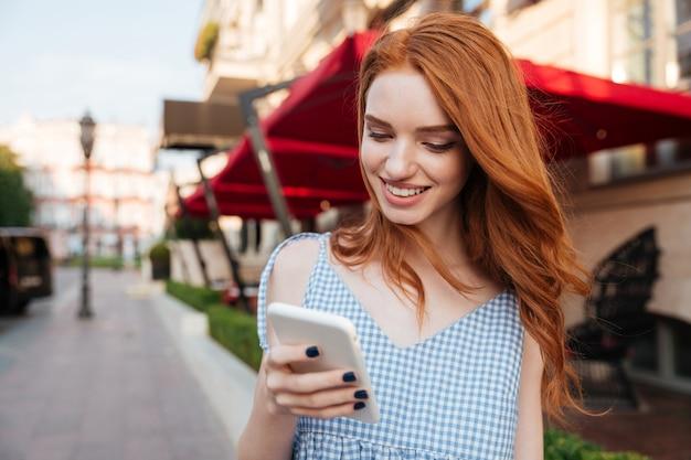 Femme rousse joyeuse aux cheveux longs à l'aide de téléphone portable tout en