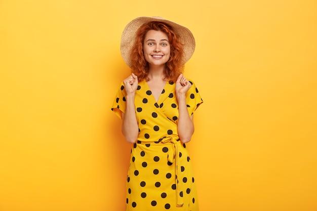 Femme rousse joyeuse posant en robe à pois jaune et chapeau de paille
