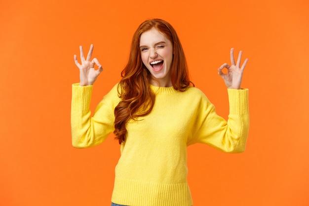 Femme rousse joyeuse et positive, enthousiaste en pull jaune avec un clin de œil d'approbation