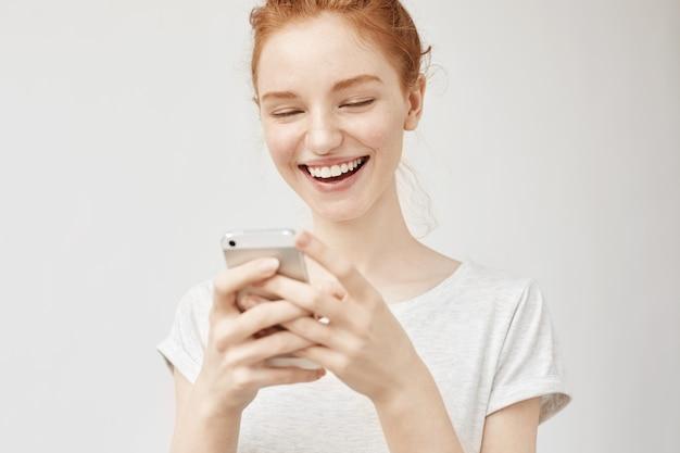 Femme rousse joyeuse souriante regardant l'écran du téléphone.