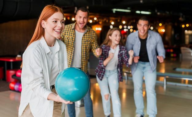 Femme rousse lançant une boule de bowling turquoise