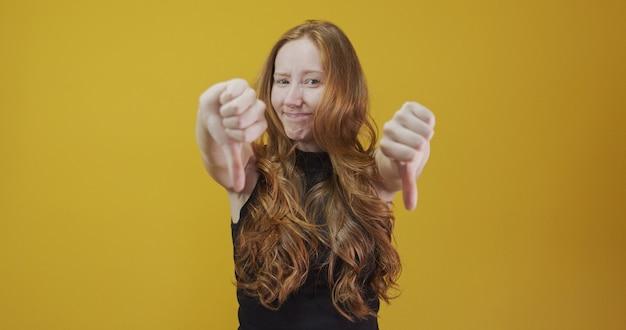 Femme rousse malheureuse donnant un geste vers le bas regardant avec une expression négative et une désapprobation