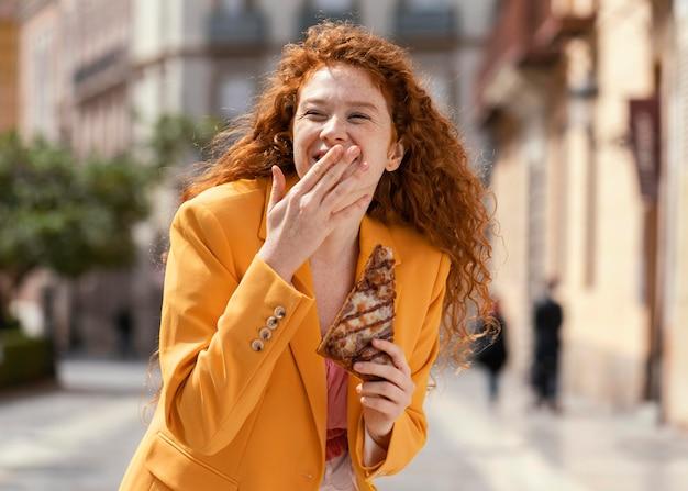 Femme rousse mangeant de la nourriture de rue