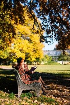 Femme rousse en manteau à carreaux et béret noir lisant un livre sur un banc se reposant dans un parc d'automne à une journée ensoleillée