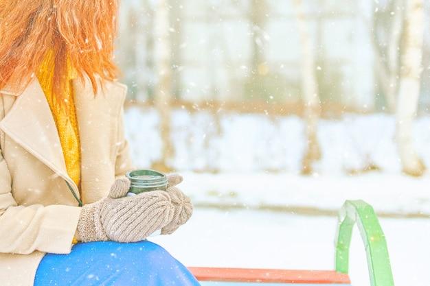 Femme rousse en manteau, pull jaune, pantalon bleu, mitaines boit du café pour aller