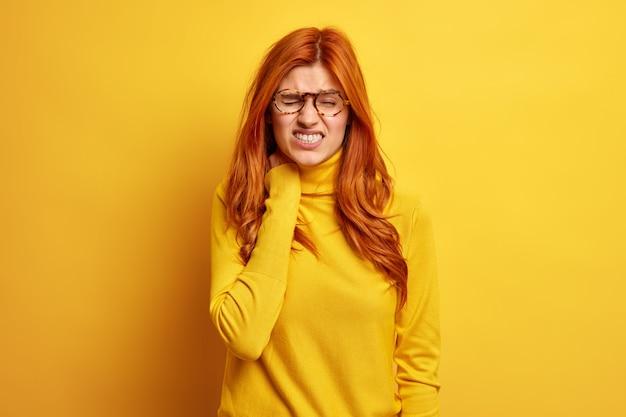 La femme rousse mécontente touche le cou ressent une forte douleur a un syndrome de bureau mène un mode de vie sédentaire porte des lunettes à col roulé.