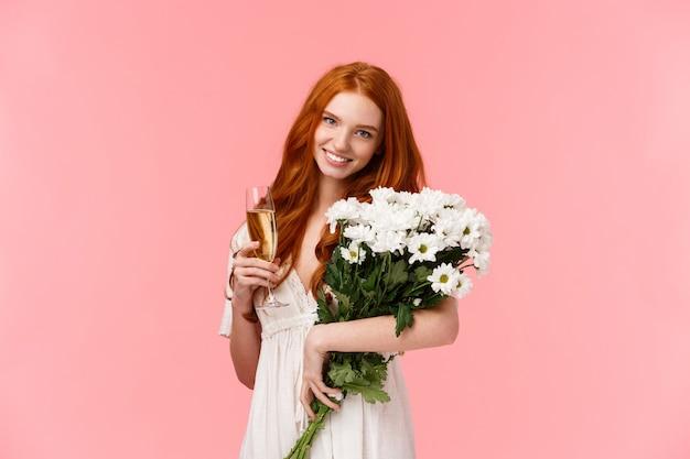 Une femme rousse mignonne et tendre reçoit un beau cadeau bouquet, tenant des fleurs blanches