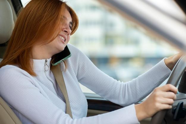 Femme rousse parlant sur son téléphone portable au volant d'une voiture.