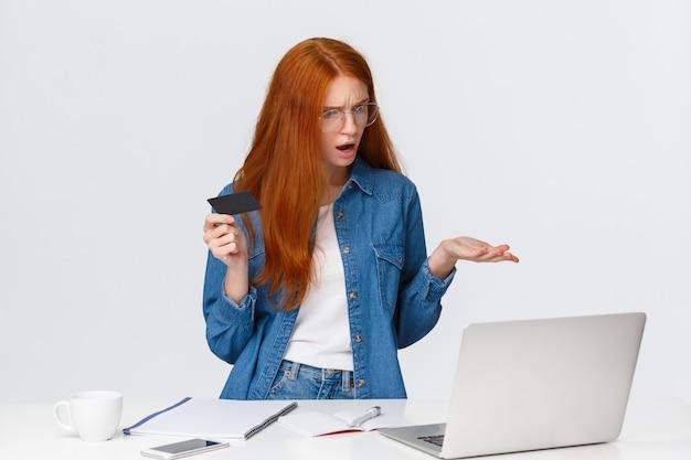 Une femme rousse perplexe et confuse ne peut pas faire d'achat en ligne, je ne sais pas pourquoi un problème de transfert d'argent est survenu, haussant les épaules avec consternation à l'écran de l'ordinateur portable, détenez la carte de crédit, plaignez