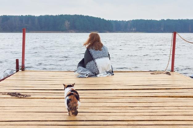 Femme rousse en plaid assis sur la jetée du lac en automne et à la recherche lointaine.