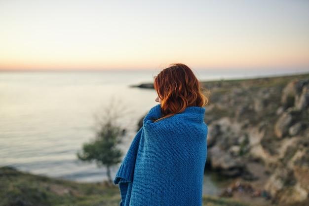 Femme rousse avec un plaid bleu à l'extérieur de l'air frais de voyage