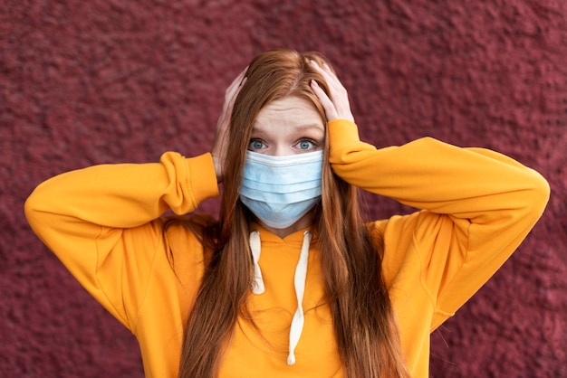 Femme rousse portant un masque facial