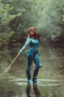 Femme rousse posant avec costume de super-héros