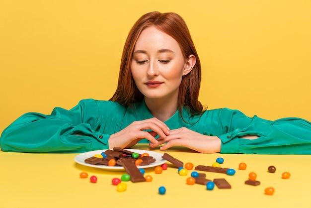 Femme rousse posant avec différents bonbons