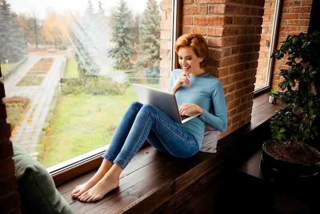Femme rousse posant près de la fenêtre à la maison