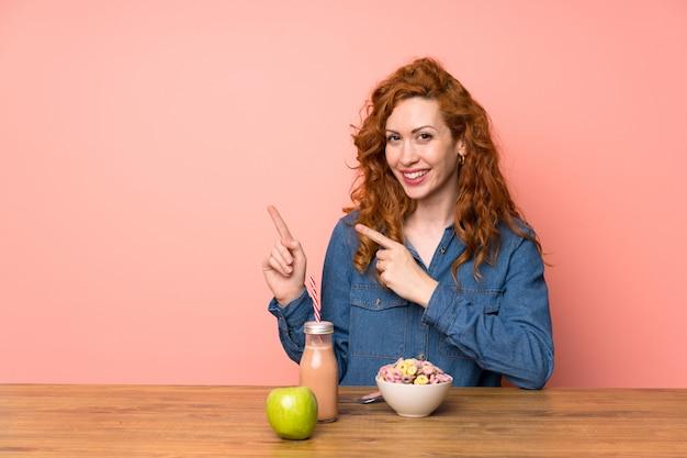Femme rousse prenant des céréales pour le petit déjeuner et un fruit en pointant le doigt sur le côté