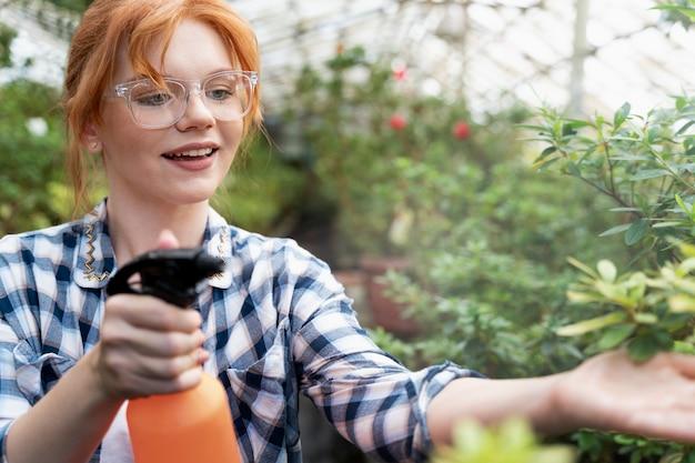 Femme rousse prenant soin de ses plantes dans une serre