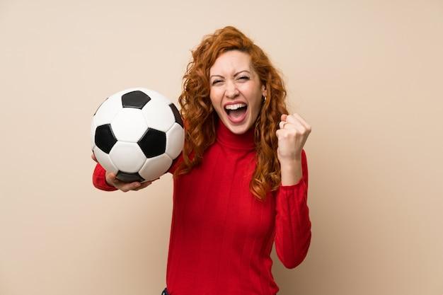 Femme rousse avec un pull à col roulé tenant un ballon de foot