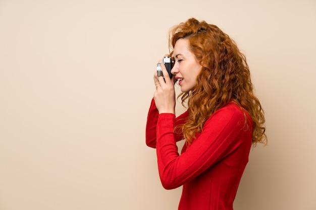 Femme rousse avec un pull à col roulé tenant une caméra