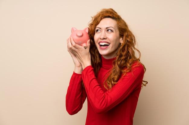 Femme rousse avec un pull à col roulé tenant une grande tirelire