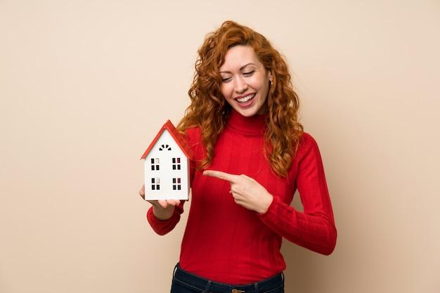 Femme rousse avec un pull à col roulé tenant une petite maison