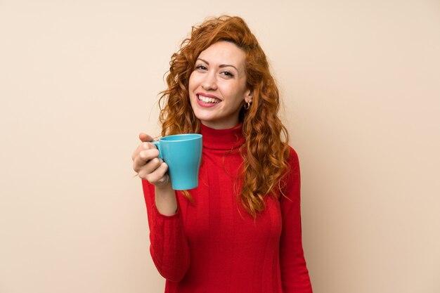Femme rousse avec pull à col roulé tenant une tasse de café