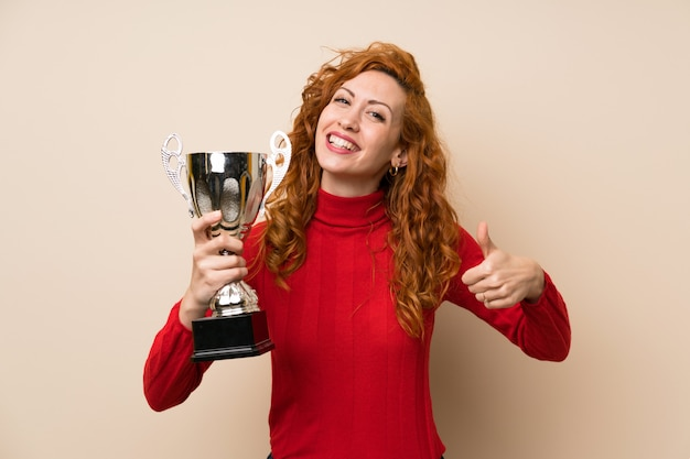 Femme rousse avec un pull à col roulé tenant un trophée