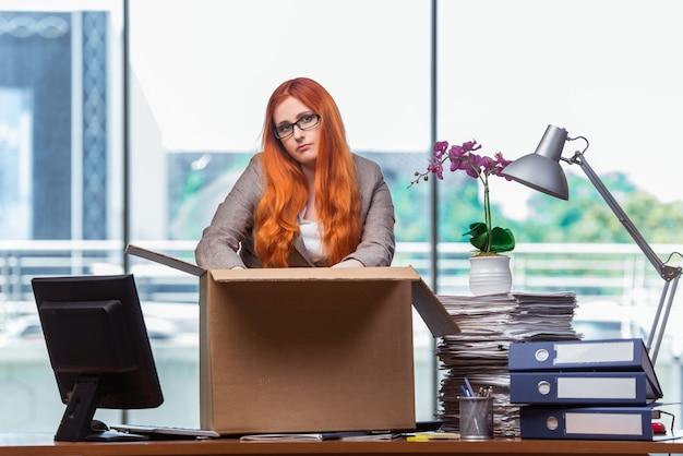 Femme rousse qui déménage dans son nouveau bureau et qui range ses affaires