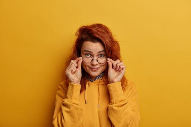 Femme rousse regarde scrupuleusement à travers des lunettes optiques, a un regard curieux, garde les mains sur la monture de lunettes, porte un sweat-shirt jaune