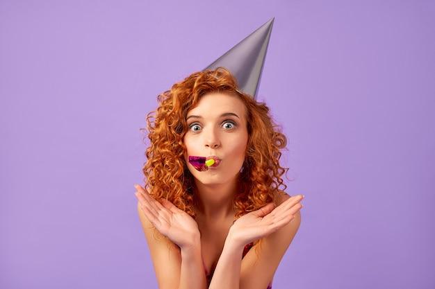 Femme rousse en robe brillante et casquette de fête soufflant dans un sifflet isolé sur violet