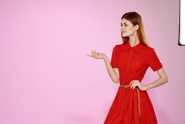 Femme rousse en robe rouge gestes de la main fond rose de luxe. photo de haute qualité