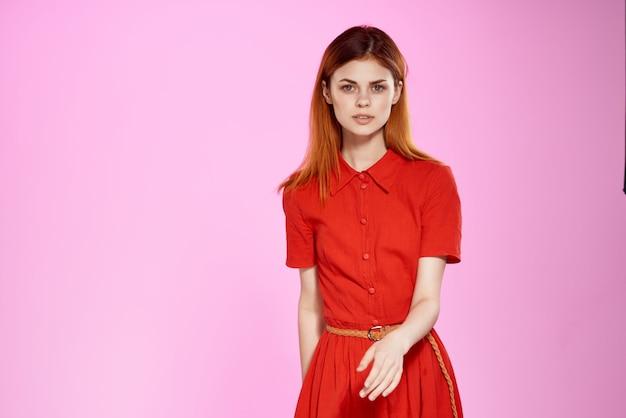 Femme rousse en robe rouge posant un studio look attrayant