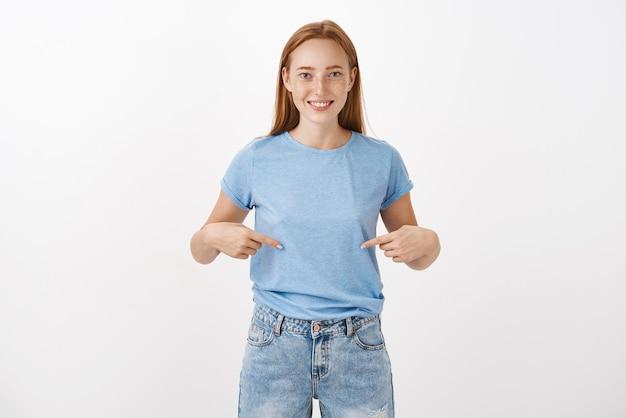 Femme rousse satisfaite heureuse perdre du poids pour la saison du bikini debout en t-shirt bleu décontracté pointant sur le ventre ou la poitrine avec un sourire heureux debout joyeux et détendu