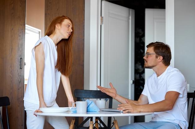 Une femme rousse se dispute avec un homme qui travaille à la maison