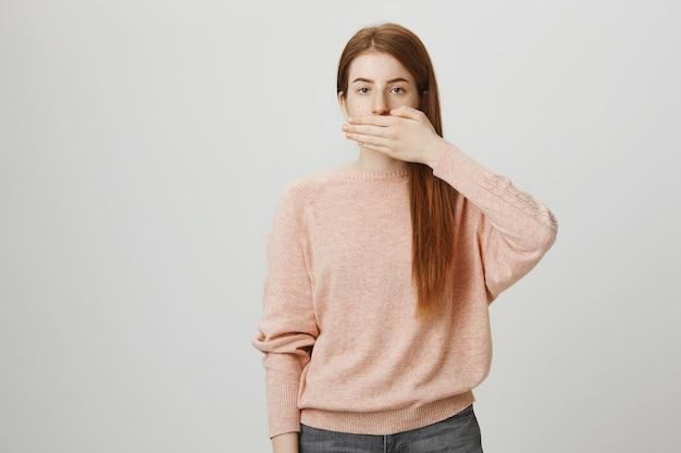 Femme rousse sérieuse ferme la bouche avec la paume, reste silencieuse