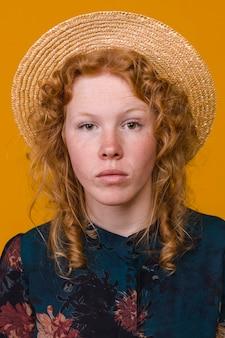 Femme rousse sérieuse en studio avec fond coloré
