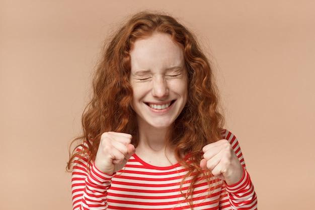 Femme rousse serrant les poings et clignant des yeux comme si elle soutenait quelqu'un