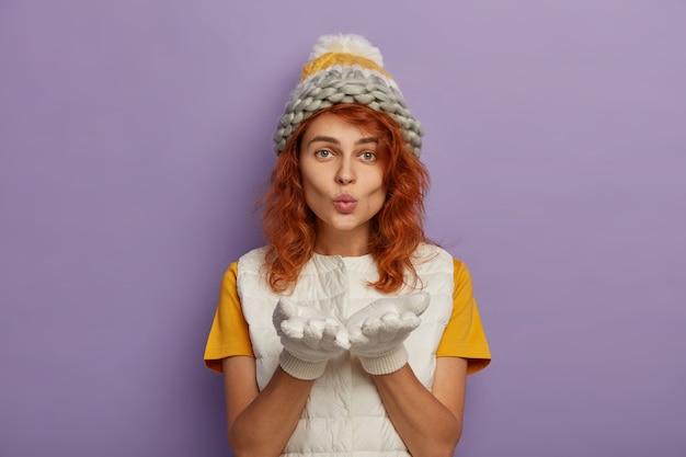 Femme rousse souffle à la caméra, garde les paumes vers l'avant, porte un bonnet tricoté et un gilet blanc, profite de l'hiver