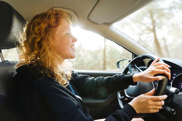 Femme rousse souriante au volant d'une voiture