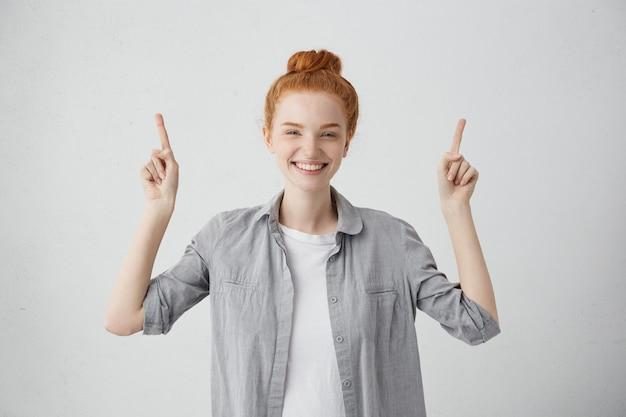 Femme rousse souriante aux taches de rousseur avec de beaux yeux bleus debout, levant son doigt indiquant quelque chose.
