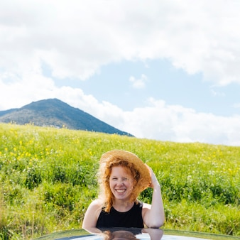 Femme rousse souriante dans la nature