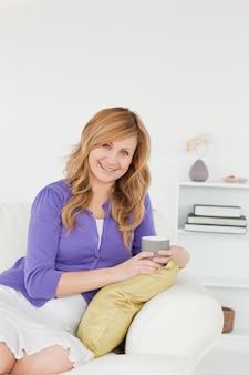 Femme rousse souriante posant assis sur un canapé