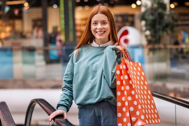 Femme rousse souriante tenant un sac à provisions