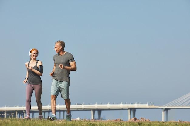 Femme rousse sportive dans des écouteurs sans fil jogging avec son petit ami et discuter avec lui