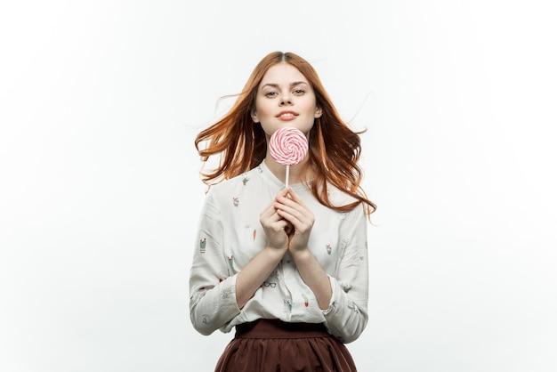 Femme rousse avec sucette dans les mains émotions mode de vie de bonbons amusants