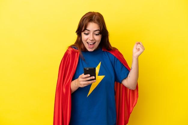 Femme rousse super héros isolée sur fond jaune surpris et envoyant un message