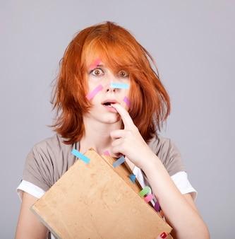 Femme rousse surprise avec livre et notes sur le visage.