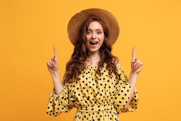 Femme rousse surprise posant en robe jaune avec des manches pointant vers le haut par les doigts sur le jaune.