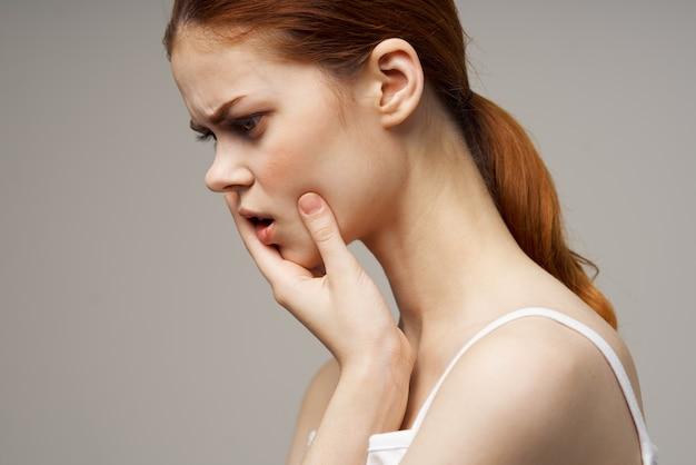 Femme rousse tenant la main près du visage sur la vue de côté de fond gris. photo de haute qualité