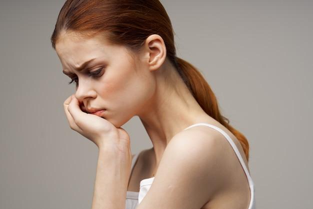 Femme rousse, tenant la main près du visage sur la vue de côté de fond gris